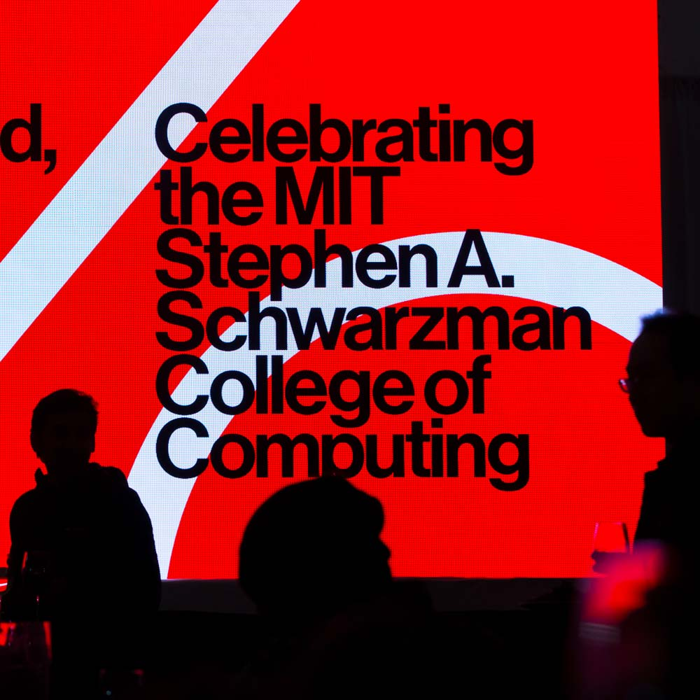 Image of a screen with black text on a red background during the inaugural event launching the College of Computing.