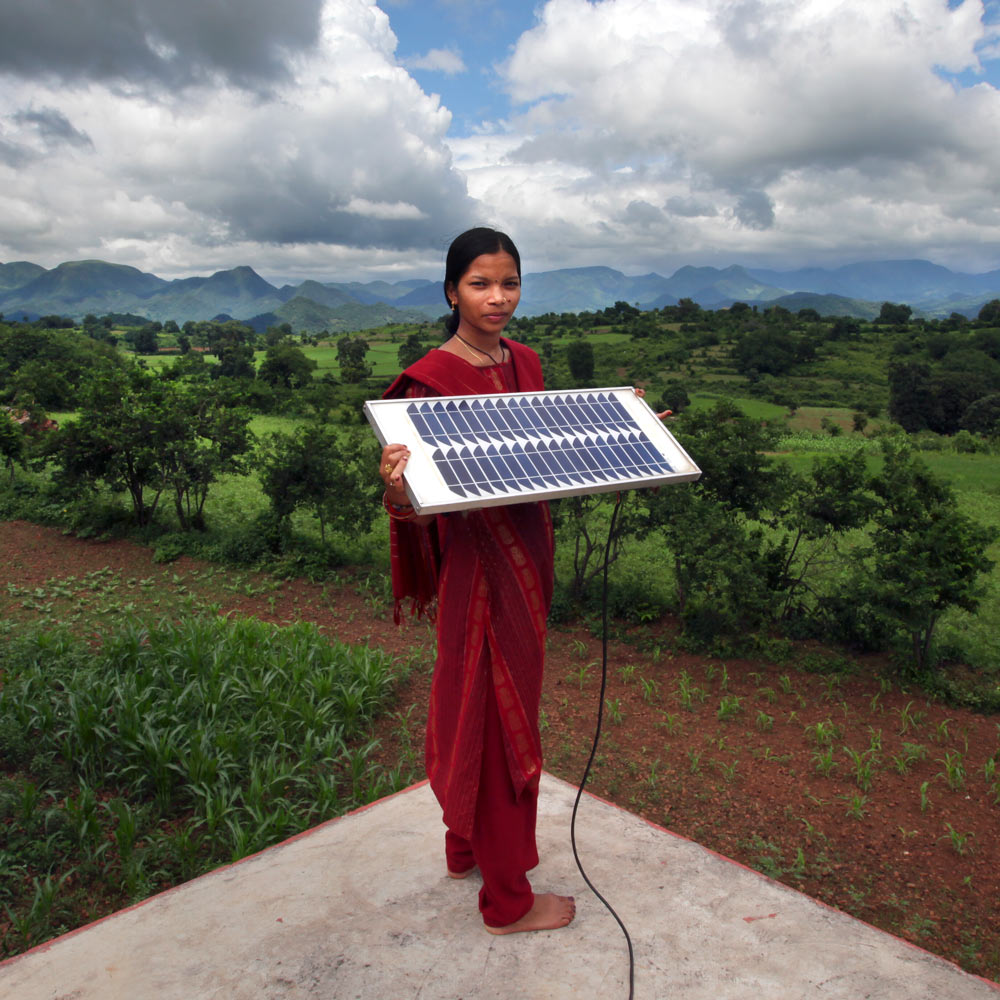 Woman from a rural part of India holds a solar panel.