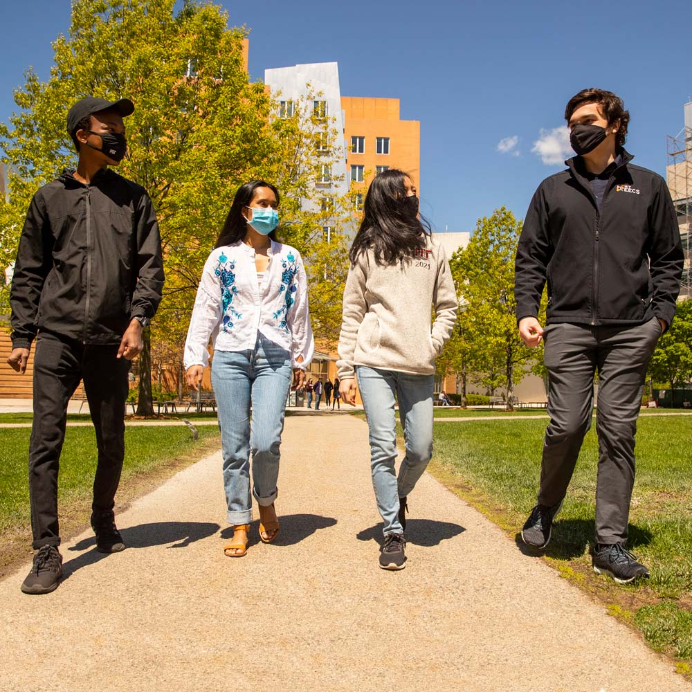 Image of four students walking on campus.