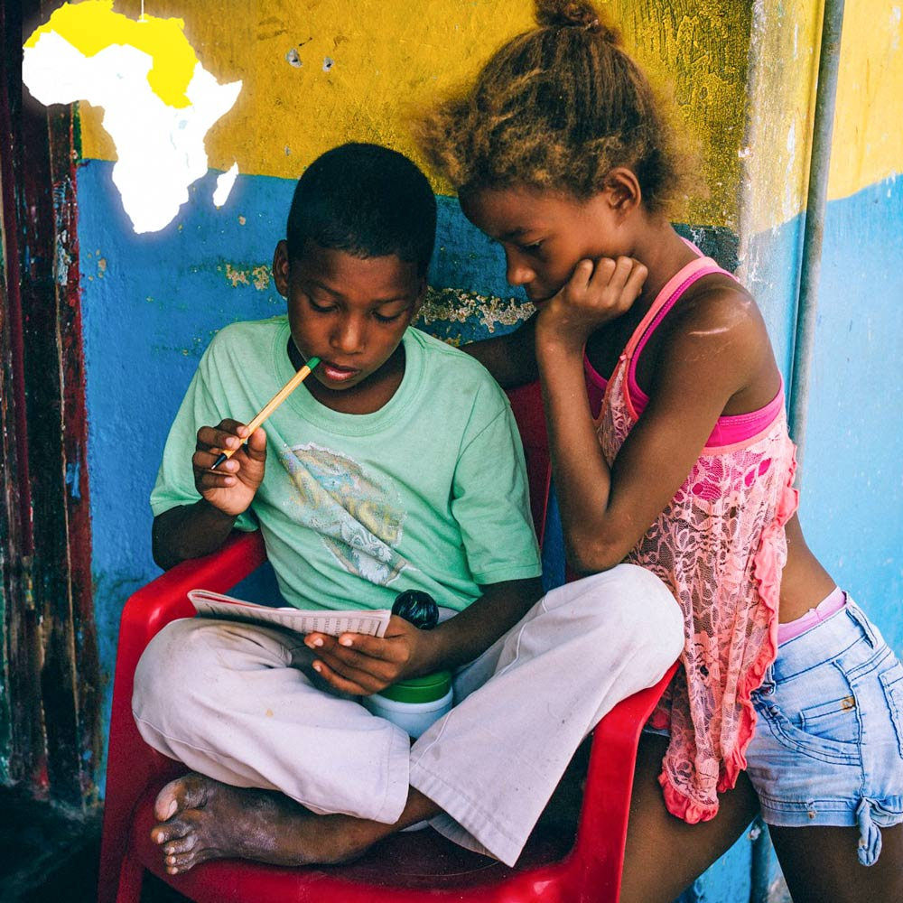 Image of two youths studying a booklet.